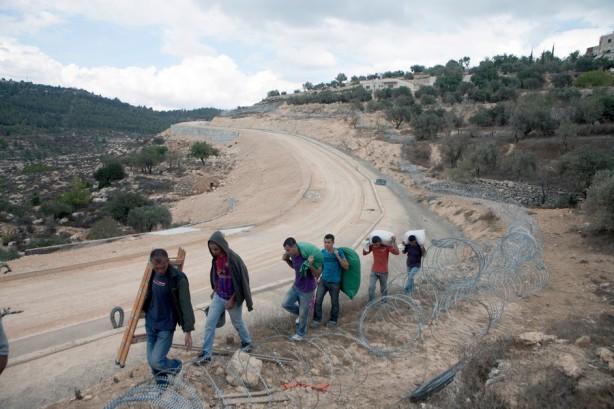 Miembros de la familia Atrash cargan con equipo y con aceitunas a través de las montañas por la ruta del muro después de cosechar sus tierras del otro lado de la barrera, octubre 2012. La familia posee más de cuatro dunums en el valle de al-Walaja. Sólo pueden llegar a sus tierras caminando  a través de la montaña y pasando por un hueco en el muro.