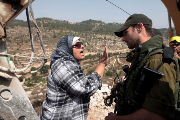 """Shireen al-Araj, una prominente activista en la lucha contra el muro, confronta a un soldado israelí durante  una protesta. Dice, """"Esto es sumoud (tenacidad). Estoy luchando día a día con mi comunidad...Aquí estamos, estamos peleando y existimos. Somos samidin (firmes)."""" (TedEx Talk, Ramallah, 24 mayo 2011)"""