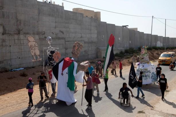 Una marcha de protesta con títeres gigantes hechos en el pueblo pasa por el muro de separación cerca del asentamiento de Gilo, septiembre de 2012. Har Gilo, establecido durnte los 1970's, está construido en la tierra de al-Walaja y de Beit Jal. Todos los asentamientos israelíes en la Cisjordania ocupada son ilegales bajo el derecho internacional.