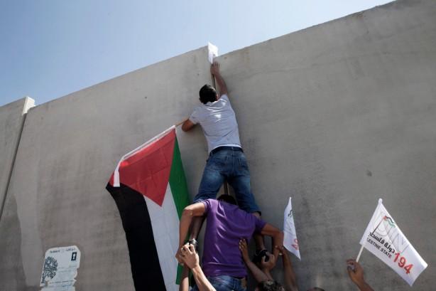 Un palestino trepa el muro de separación para alzar la bandera palestina enfrente del asentamiento Har Gilo, durante una manifestación, septiembre 2011