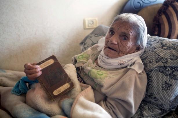 Absiya Jafari, de más de cien años de edad, sostiene un pasaporte palestino emitido durante el Mandato Británico que gobernó Palestina de 1923 a 1948, que pertenecía a su esposo y a ella, noviembre de 2013. El pueblo original de al-Walaja fue completamente destruido en 1948 durante el Nakba – la limpieza étnica que llevó al establecimiento de israel en 1948 – y todos los pobladores fueron obligados a marcharse y convertirse en refugiados. Mucho huyeron a Jordania, Líbano y el área de Belén. Hoy, el 97% de los residentes en al-Walaja son refugiados.