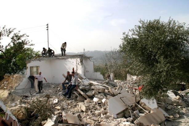 """Palestinos en los restos de la casa de Khader Rabah, demolida por las fuerzas de ocupación israelí el 22 de marzo de 2006. Casi toda la zona de al-Walaja que se encuentra actualmente en el lado reducido de  Cisjordania fue designado como """"Área C"""" después de la firma de los tratados de Oslo en 1993, otorgando completa autoridad a los militares israelíes. De hecho, los dueños de casas en casi todo al-Walaja – aquellos en el """"Área C"""" y aquellos en """"Jerusalén"""" – necesitan obtener de israel permisos de construcción para cualquier estructura construida después de 1967. Como estos permisos son prácticamente imposibles de obtener  y los palestinos no tienen otra opción más que construir de cualquier manera, muchos residentes han viuvido por múltiples demoliciones de sus casas y otras formas de acoso."""