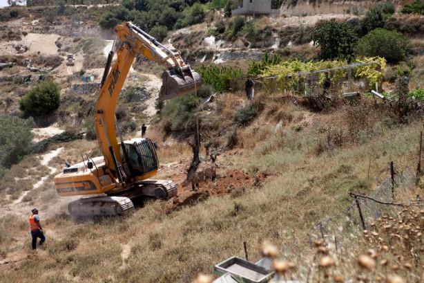 Un bulldozer saca de raíz árboles de oliva en la tierra de Ahmed Barghouth (conocido en el pueblo como Abu Nidal) para la preparación de la construcción del muro de separción, junio de 2010. La tumba de los padres de Abu Nidal y 40 dunums de su tierra están ubicados en el otro lado de la ruta de l muro.
