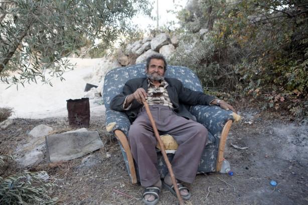 """Mohammad Awadallah, 72, cerca de su casa. noviembre 2013. Su casa fue dañada po explosiones cuando el ejército israelí voló partes de la montaña para ampliar la ruta del muro de separación y es dueño de dos dunums del otro lado del muro. Dijo """"el impacto del muro es que ahora estamos en prisión y hemos perdido nuestra tierra. Además habrá una puerta a la entrada del pueblo, lo que causará un colapso en nuestras  vidas."""""""