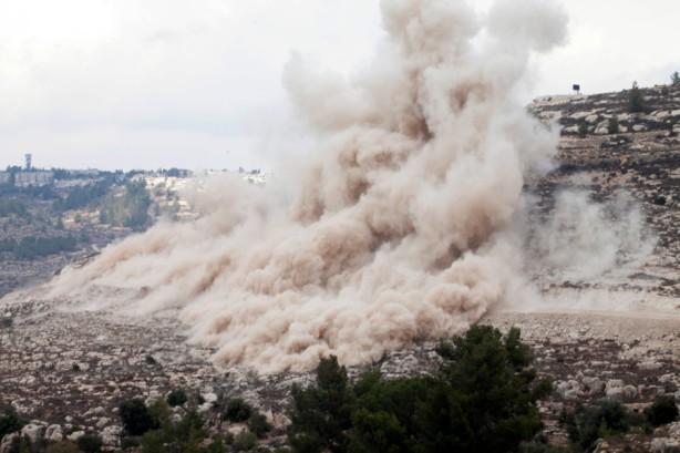 Una enorme nube de polvo se mantiene en el aire después de una explosión, en donde el ejército israelí voló partes de la montaña para despejar la ruta del muro, noviembre 2011. Una serie de explosiones causó daño a las casas cercanas.