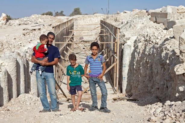 """Omar Hajajlah y sus tres hijos frente a la construcción de un túnel enfrente de su casa, octubre 2011. La casa familiar fue dejada enel """"otro"""" lado de la ruta del muro de separación. El túnel será la única conexión de la casa al pueblo y el hogar será completamente rodeado por una barrera electrificada de cuatro metros de altura. Hajajlah trabaja en Jerusalén oriental. Desde que empezó la construcción del muro enfrente de su casa, ha sido hospitalizado dos veces debido a problemas cardiacos. También una puerta militar fue puesta frente a su casa bloqueando el camino que lleva al Monasterio Cremisan y a la escuela de las Hermanas Salesianas, donde acuden sus hijos. En lugar de un viaje de unos cuantos minutos a la escuela, tienen que desvíarse  varios kilómetros."""
