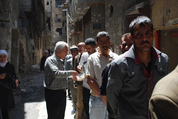 Hombres en fila para recibir paquetes de comida en un área de distribución cercana al campo Yarmouk cerca de Damasco, el 24 de abril 2014. Conforme se difundió la noticia, cientos de desesperados civiles se reunieron en el área en los siguientes días.(unrwa.org)