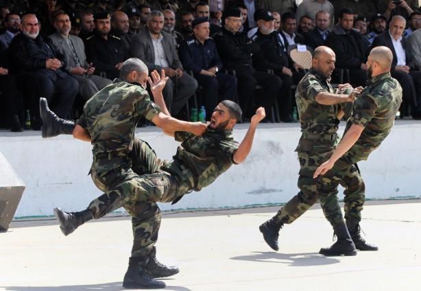 Las fuerzas de seguridad palestinas demuestran sus habilidades en un escenario donde simulan una irrupcióin en una base militar durante la ceremonia de graduación en la Ciudad de Gaza, el 17 de abril. (Yasser Qudih / APA images)