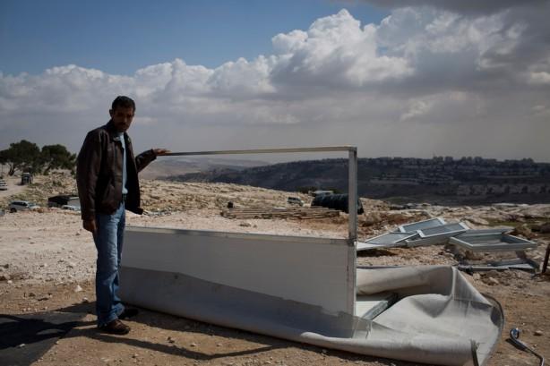 """Con el trasfondo del asentamiento israelí de Maale Adumim, un hombre palestino está parado cerca de su  casa demolida en la comunidad de Jabal al Baba en el área """"E1"""" cerca de Jerusalén, el 10 de abril. Las fuerzas israelíes demolieron  tres casas financiadas por donanates y emitieron 18 órdenes de demolición para casas en el área. (Oren Ziv / APA images)"""