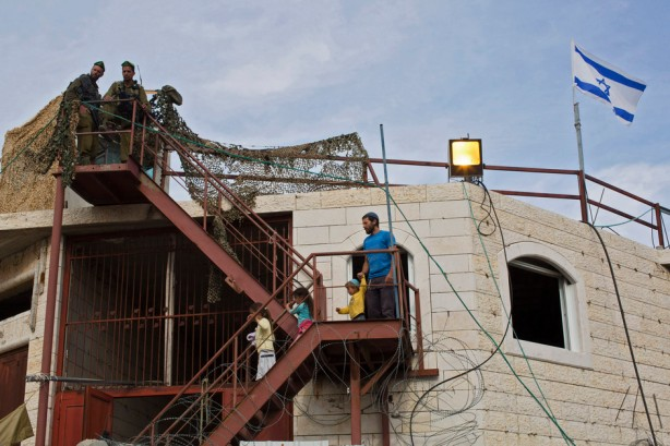 Soldados israelíes escoltan a colonos judíos mientras entran en el edificio al-Rajabi en la ciudad de Hebron en Cisjordania, el 13 de abril. Una batalla legal de años de duracióm culmina con la autorización del Ministro de Defensa Moshe Yaalon para que tres familias judías se instalen en la casa. El nuevo edificio tipo fortaleza es el primer nuevo asentamiento en Hebron desde la década de los 1980s. (Keren Manor / ActiveStills)