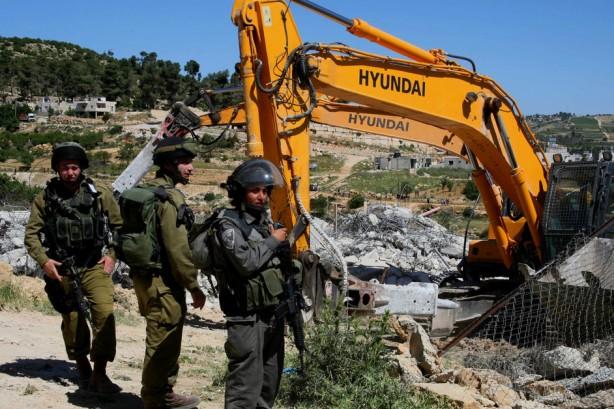 Fuerzas israelíes montan guardia mientras bulldozers demuelen una casa en el campo de refugiados de al-Aroub cerca de la ciudad de Herbrón en Cisjordania el 30 de abril. Las casas fueron demolidas por falta de permiso después de que los residentes solicitaron los permisos de construcción que les fueron negados debido a supuentos incumplimientos con las regulaciones necesarias. Los palestinos enfrentan sevras restricciones para la construcción en Cisjordania mientras los asentamientos israelíes  reciben masivas ofertas de edificación. (Mamoun Wazwaz / APA images)