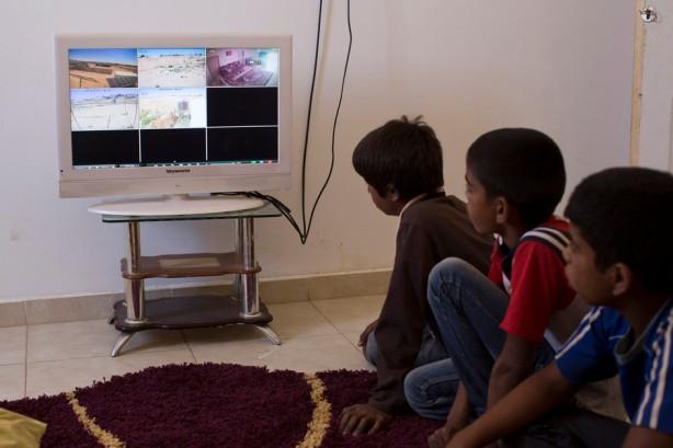 Niños de la famili Adsan ven un video de oficiales de la administración civil y policías entrando a su casa para entregarles una orden de demolición de esa misma casa en el pueblo beduino de Bir-Hadaj en el desierto de Naqab (Negev) el 27 de abril. Bir-Hadaj fue reconocido por el gobierno israelí en 1999 y su plan de urbanización fue aprobado en 2003 pero el pueblo aún carece de infraestructura básica y sus habitantes frecuentemente enfrentan órdenes de demolición y trato severo por parte de la policía. (Keren Manor / ActiveStills)
