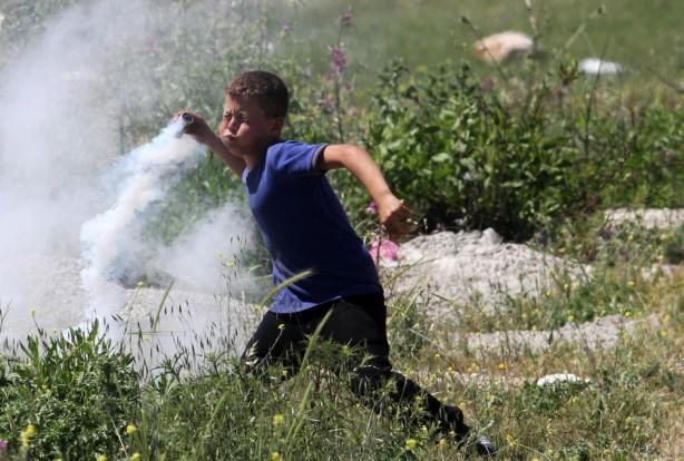 Un chico palestino en el pueblo de Nabi Saleh crca de la ciudad Ramalla de Cisjordania, devuelve una lata de gas lacrimógeno disparado por las fuerzas de ocupación israelíes durante los enfrentamientos que resultaron por una protesta en solidaridad  con los prisioneros palestinos mantenidos en cárceles israelíes, 18 de abril. (Issam Rimawi / APA images)
