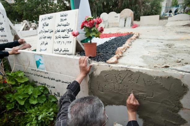 Un familiar escribe una dedicatoria provisional en la tumba de Noha Katamish hasta que su lápida grabada pueda colocarse en el cementerio del campo de refugiados de Aida, en Cisjordania, el 15 de abril. Katamish, que tenía asma murió después de que una granada de gas lacrimógeno fue disparada dentro de su casa, el día anterior. Fue enterrada junto a la tumba de Saleh Al- Amareen, que tenía 15 años cuando murió por un diparo en la cabeza por las fuerzas israelíes en el campo de refugiados Aida en enero de 2013. (Ryan Rodrick Beiler/ActiveStills)