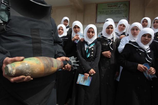 Un miembro de las fuerzas de seguridad palestinas sostiene un cartucho de mortero mientras explica a estudiantes los daños de las municiones sin explotar en la escuela de Khan Younis al sur de la Franja de Gaza, 7 de abril. (Ashraf Amra / APA images)