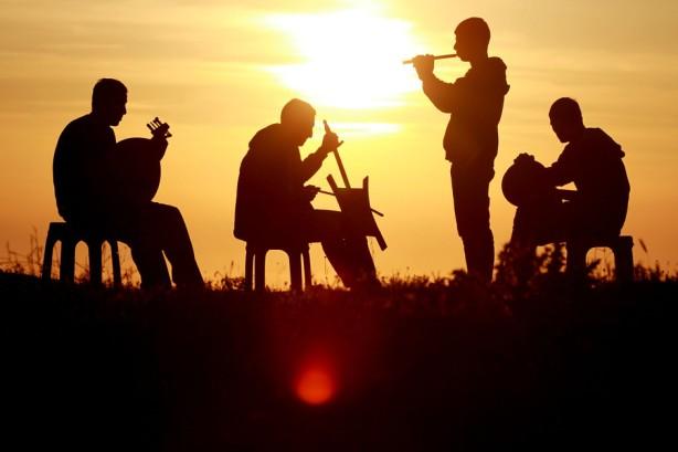 Jóvenes palestinos en una interpretación musical durante la puesta de sol en la ciudad de Ramallah en Cisjordania, el 22 de abril. (Shadi Hatem / APA images)