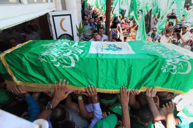 Dolientes en la ciudad de Ramallah en Cisjordania ondean la bandera verde del movimiento político islámico de Hamas mientras asisten , el 30 de abril, al funeral de dos miembros de Hamas, Adel e Imad Awadallah, quienes fueron asesinados en1998. Israel regresó los restos de cuatro palestinos a sus familias ese día.