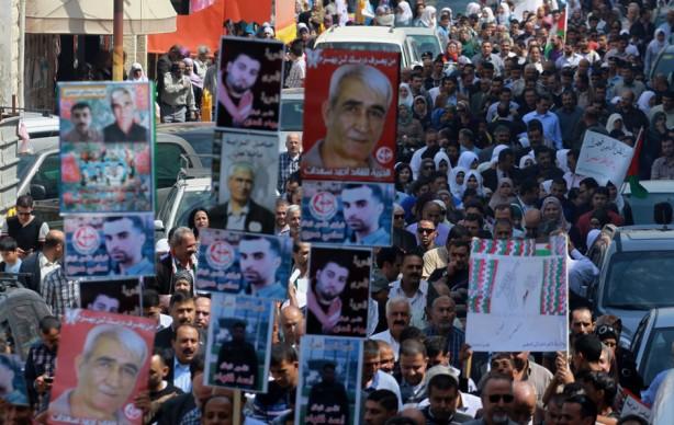 Los palestinos sostienen fotografías de prisioneros palkestinos durante una coincentración que señal el Día del Prisionero Palestino en la ciudad de Tulkarem en Cisjordania, el 17 de abril. Actualmente Israel mantiene a más de 5,000 prisioneros políticos palestinos. (Nedal Eshtayah/APA images)