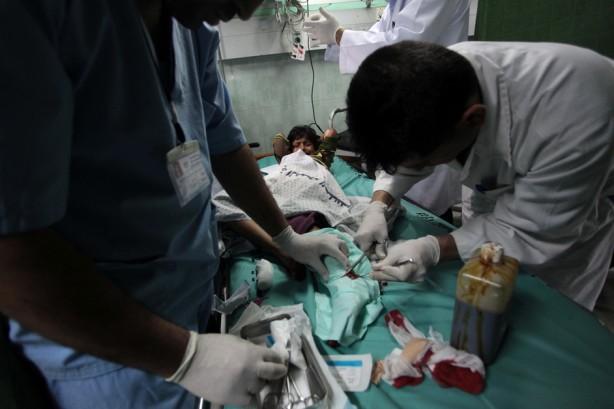 Doctores palestinos tratan a un niño herido en el hospital después de un ataque aéreo por aviones de guerra israelíes en Beit Lahia, al norte de la Franja de Gaza el 23 de abril. El ataque se dio mientras miles de palestinos tomaban las calles de la Ciudad de Gaza para celebrar el anuncio por Hamas y la Organización para la Liberación de Palestina de un acuerdo para formar un gobierno de unidad y terminar con los siete años de administrzación dividida. (Ashraf Amra / APA images)