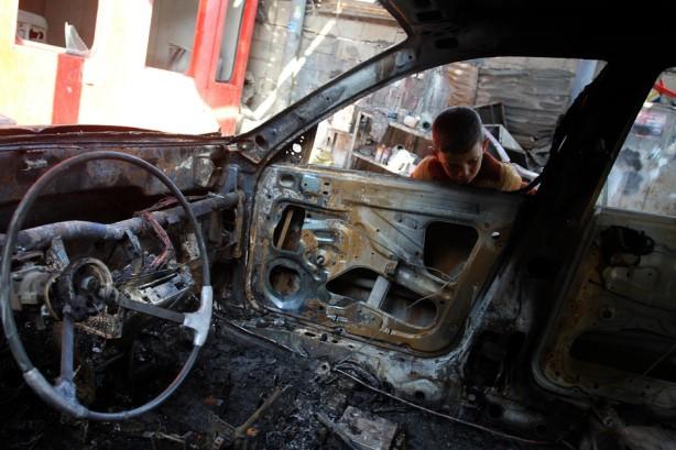 Un niño palestino inspecciona un coche quemado después de los ataques aéreos israelíes durante la noche al norte de la Franja de Gaza el 4 de abril. Después de que Israel cancelara la liberación de 26 prisioneros palestinos el día anterior, los palestinos en Gaza lanzaron 4 cohetes al norte de Israel dando lugar a los taues aéreos en represalia. (Mohammed Asad / APA images)