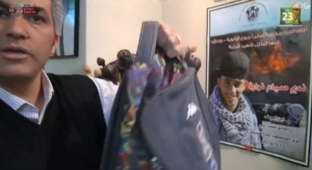 Siam Nuwara muestra al canal 1 israelí la mochila de su hijo Nadim, que aparece en el póster, misma que llevaba cuando fue asesinado por un francotirador isrelí el 15 de mayo.