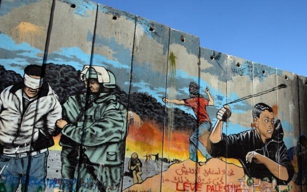 Grafiti describiendo la ocupación militar de los territorios palestinos pintado en el controversial muro israelí de separación en Bethlehem. Ian Walton/Getty Images